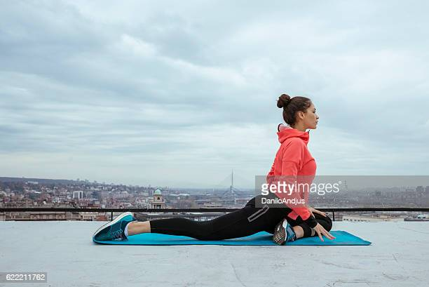 fit woman stretching and exercising on the rooftop