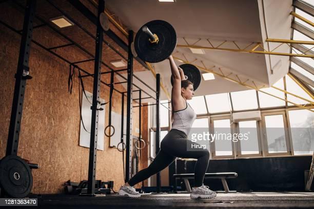 fit frau training mit gewichten im fitnessstudio - aktiver lebensstil stock-fotos und bilder