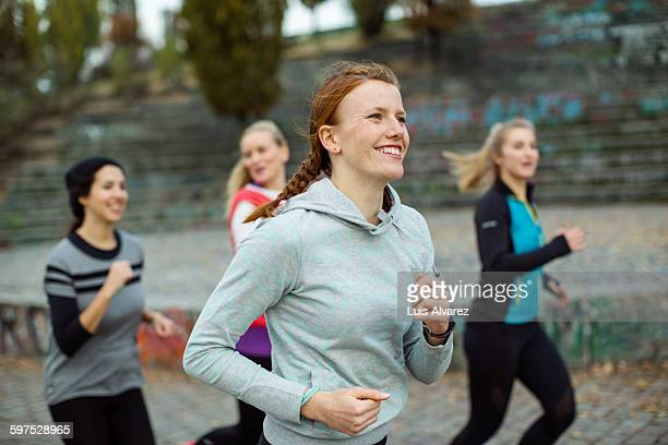 fit woman with friends jogging in park - jogging stock pictures, royalty-free photos & images