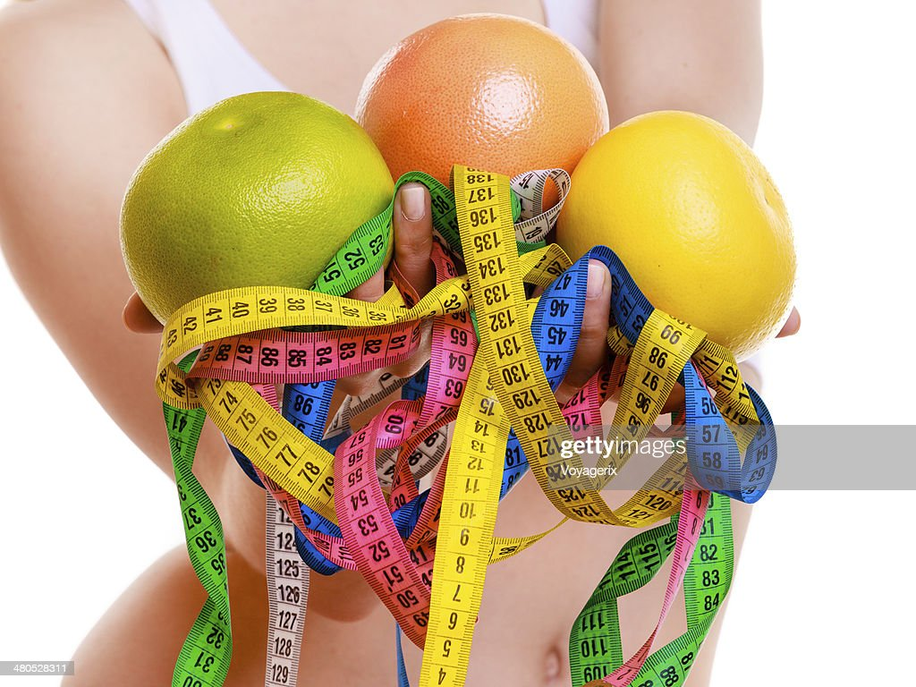Fit woman with measure tapes fruit. Time for diet slimming. : Stock Photo