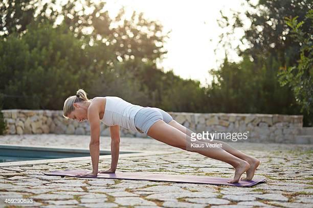 Fit yoga teacher making Plank Pose