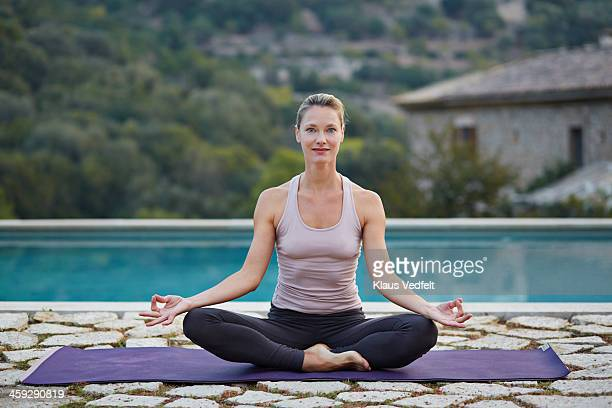 Fit yoga teacher making Sukhasana (Easy Pose)