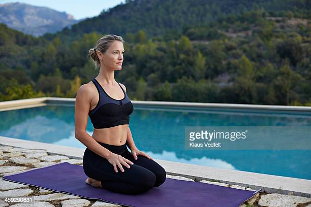 fit yoga teacher making virasana (hero pose) - klaus vedfelt mallorca stock pictures, royalty-free photos & images