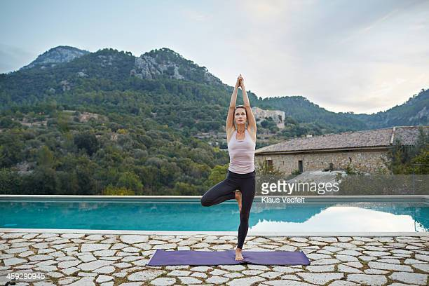 fit yoga teacher making vrksasana (tree pose) - tree position stock photos and pictures