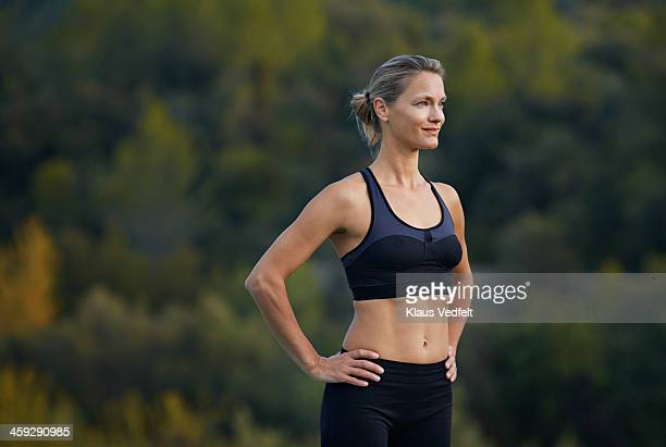 fit yoga teacher standing confident & smiling - arms akimbo stock pictures, royalty-free photos & images