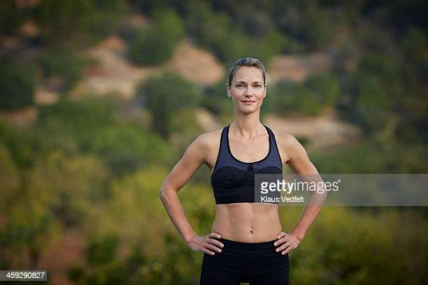 Fit yoga teacher standing & smiling confident