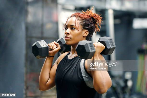 fit, young african american woman working out with hand weights in a fitness gym. - musculação com peso - fotografias e filmes do acervo