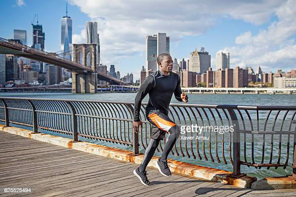 Fit young african man running on promenade