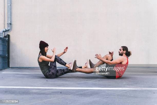 fit young couple doing partner exercises - koordination stock-fotos und bilder