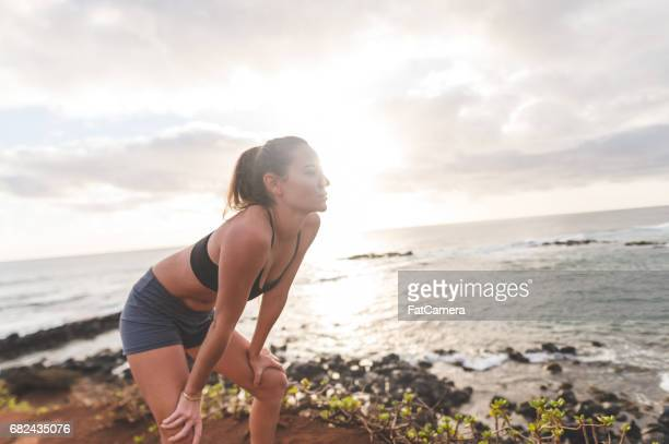 Fit young Eurasian woman takes a break from running along  Hawaii coastline