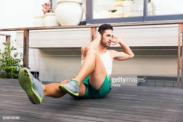 fit young man doing crunches on floorboard - treino esportivo - fotografias e filmes do acervo