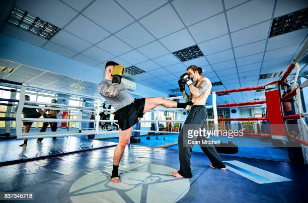 Fit young man doing kickboxing training with trainer