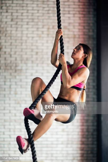 Fit young woman climbing a rope as her exercise training