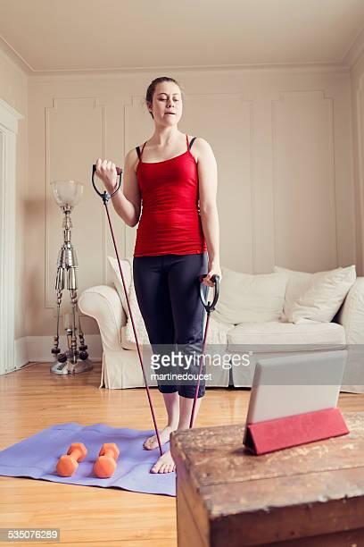 Fit jungen Frau Ausübung zu Hause mit digitalen tablet, vertikal.