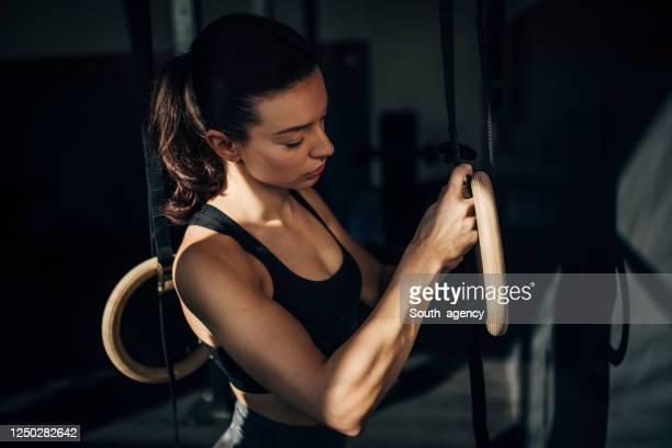 fit junge frau trainieren auf gymnastikringe in der turnhalle - frauen ringen stock-fotos und bilder