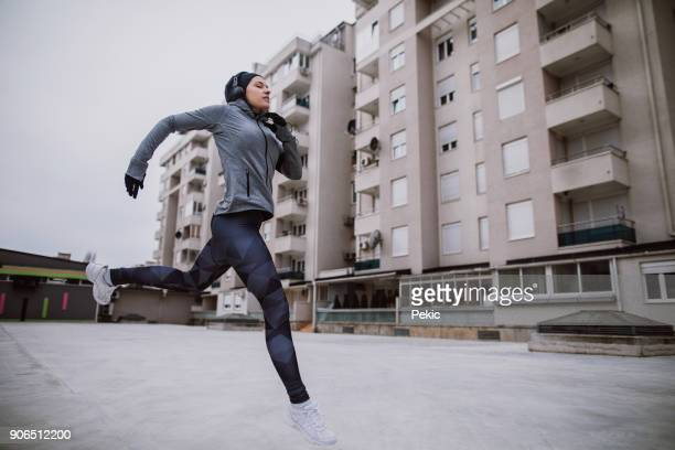 fit young woman jumping and running - center athlete stock pictures, royalty-free photos & images