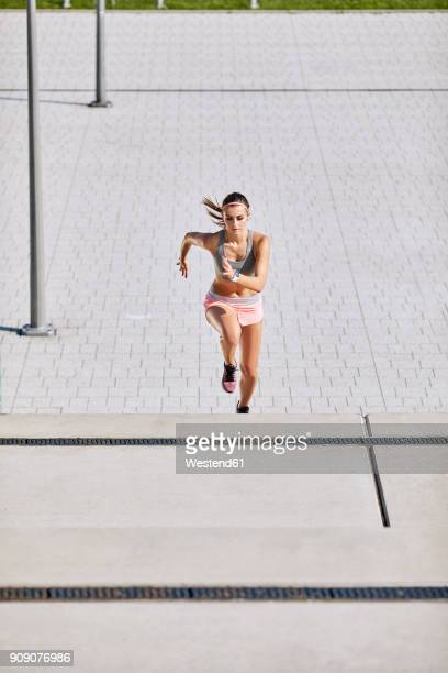 fit young woman running on stairs - one young woman only stock pictures, royalty-free photos & images