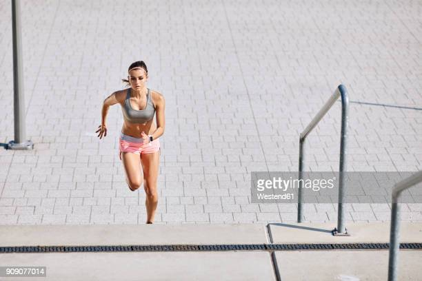 fit young woman running on stairs - approaching stock pictures, royalty-free photos & images