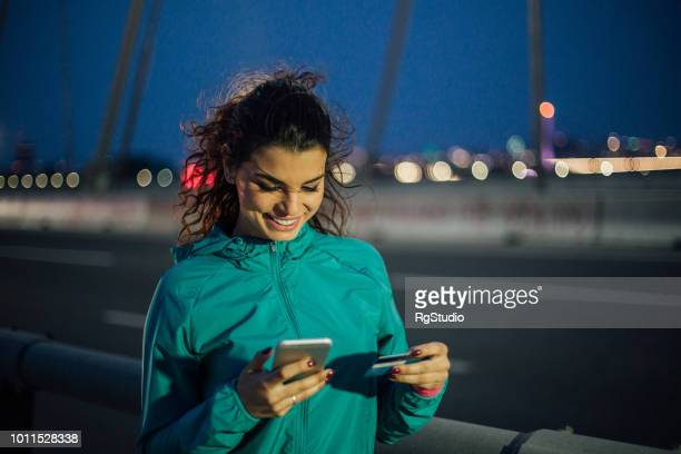 fit young woman shopping online after outdoor night exercise - charging sports stock pictures, royalty-free photos & images