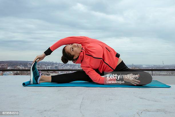 fit young woman stretching in the morning on the rooftop