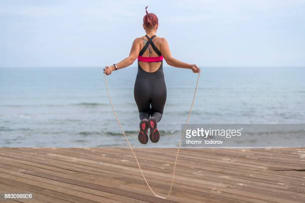 Fit young woman with tattoos jumping high on a rope near the sea