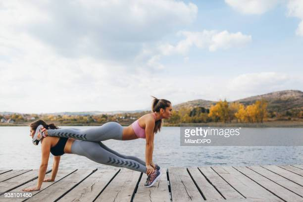 fit young women in a plank position at the lake pier - circuit training stock photos and pictures