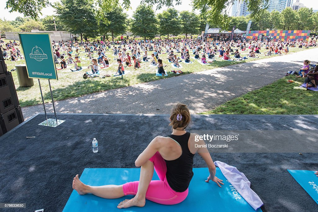 Fitbit Local Ambassador Jenny Finkel leads participants in a yoga workout during the launch of Fitbit Local Free Community Workouts In Chicago at Grant Park on July 16, 2016 in Chicago, Illinois.