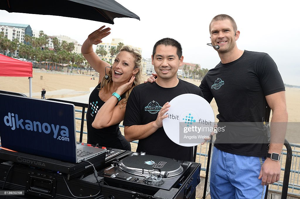 Fitbit Local Ambassadors Elise Joan and Todd McCullough pose with DJ Kanoya as Fitbit Local LosAngeles launches with a free event on the Santa Monica Pier. Fitbit Local Ambassadors Elise Joan & Todd McCullough lead participants in a bootcamp and yoga workout at Santa Monica Pier on March 5, 2016 in Santa Monica, California.
