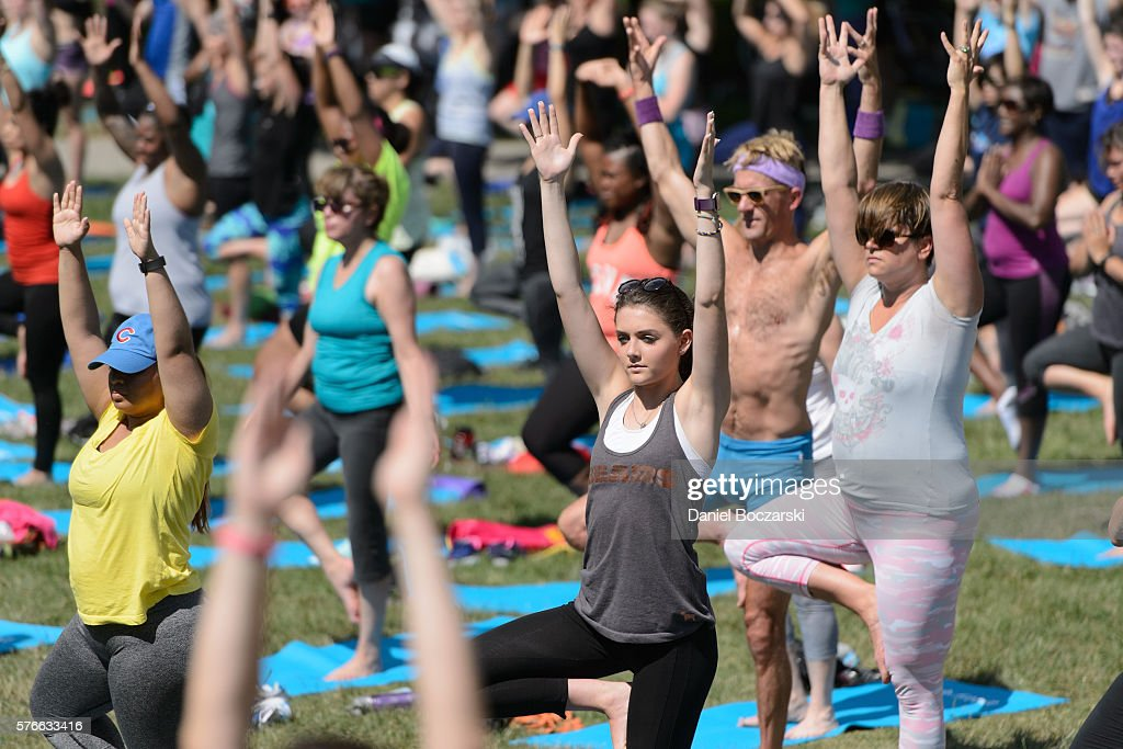 Fitbit Local Ambassadors Jeremy Walton and Jenny Finkel lead participants in a bootcamp and yoga workout during the launch of Fitbit Local Free Community Workouts In Chicago at Grant Park on July 16, 2016 in Chicago, Illinois.