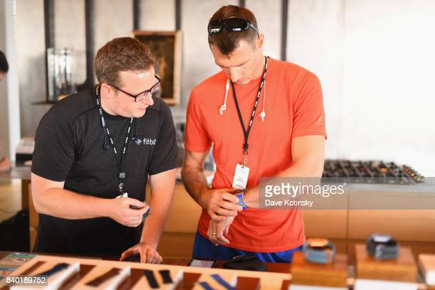 Fitbit team member assists a guest with Fitbit devices at Fitbit Day 1 on August 21 2017 in Montauk New York Fitbit introduced new products including...