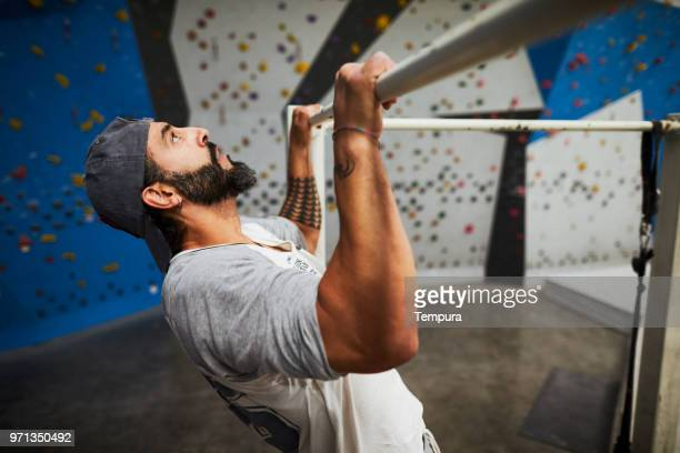fitness and warm-up in climbing gym, doing chinups. - chin ups stock photos and pictures