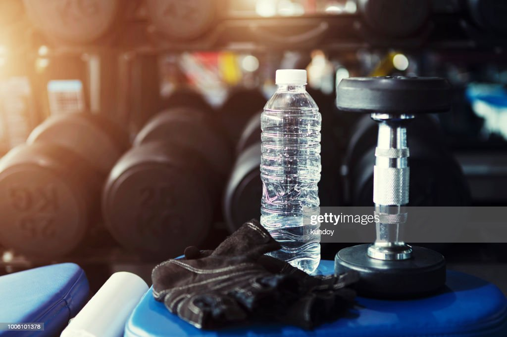 Fitness and workout concept, fresh water bottle in gym with dumbbell. : ストックフォト