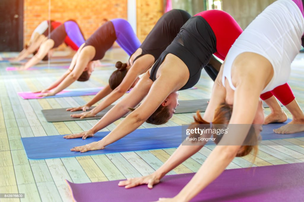 Fitness Asian Female Group Doing Namaste Yoga Pose In Row At The Class Stock