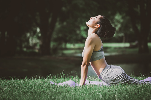 Fitness asian woman doing yoga in park 1082879824