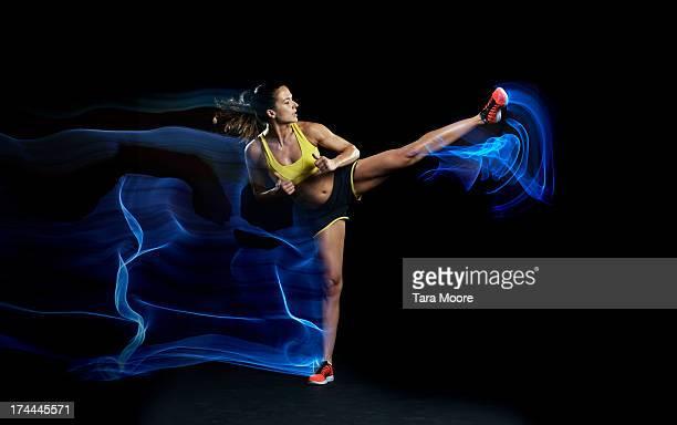 fitness athlete kicking with light trails - schoppen lichaamsbeweging stockfoto's en -beelden