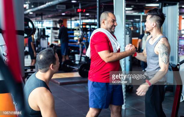 fitness center members greeting each other - center athlete stock pictures, royalty-free photos & images
