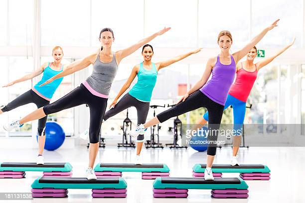 Fitness Class Doing Aerobics On Steps In Health Club