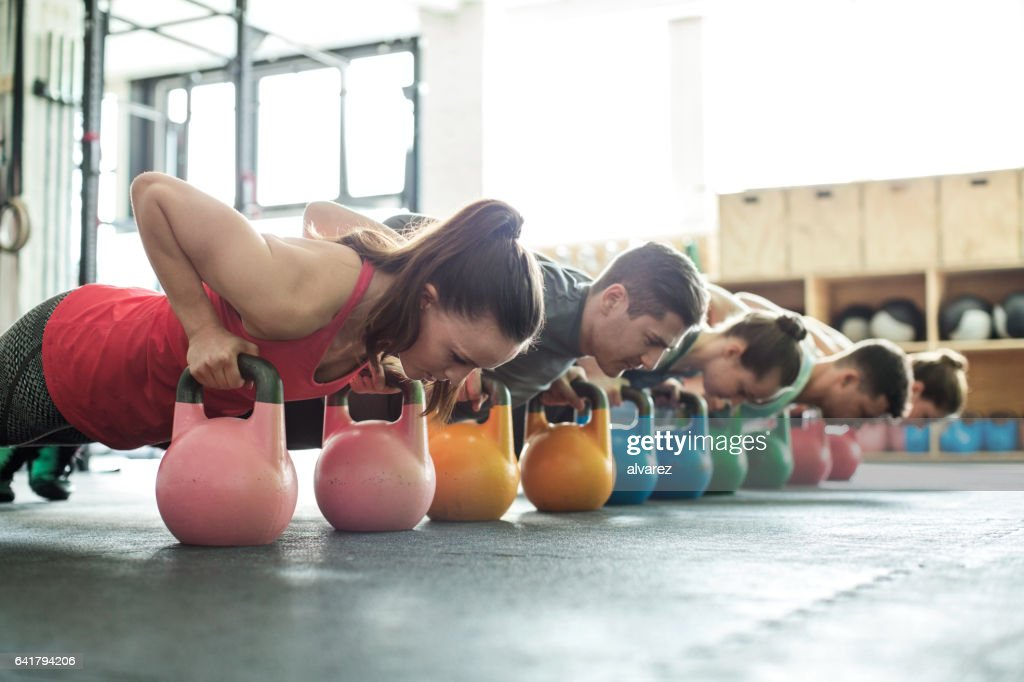 Fitness class doing push-ups with kettle-bells : Stock Photo