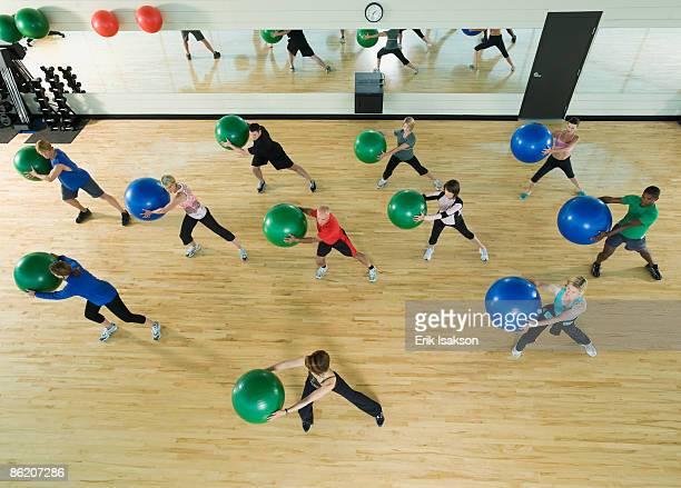 Fitness class holding balance balls