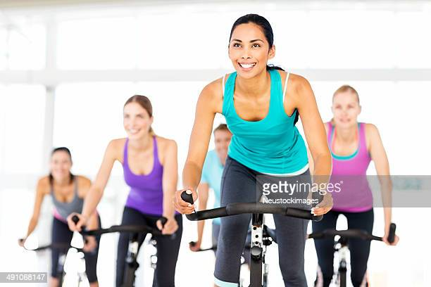 Fitness Class Looking Ahead While Spinning In Health Club