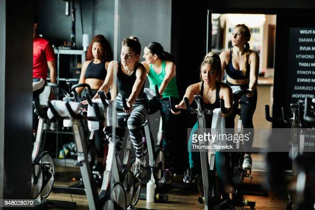 Fitness class riding stationary bikes during class in cycling studio
