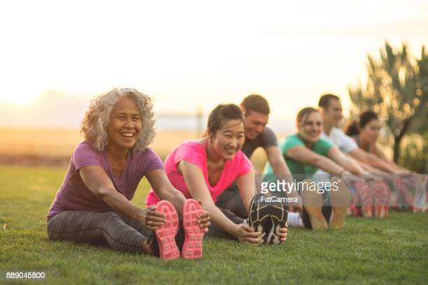 fitness class stretching - outdoors stock pictures, royalty-free photos & images