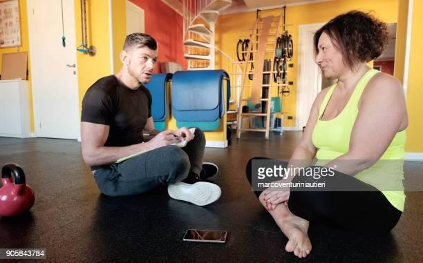 preparador físico habla sobre el programa de entrenamiento con su cliente con curvas - modelos gorditas fotografías e imágenes de stock