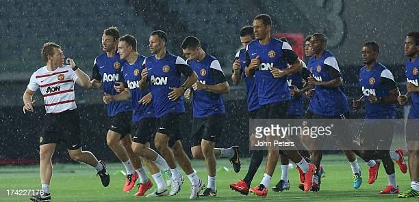Fitness Coach Gary Walker Jonny Evans Phil Jones Ryan Giggs and Rio Ferdinand of Manchester United in action during a first team training session as...