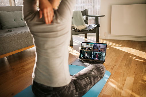 Fitness coach teaching yoga online to group of people 1219901733