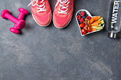 Fitness concept, pink sneakers, dumbbells, bottle of water and heart shaped plate with vegetables and berries on a grey background, top view, healthy lifestyle