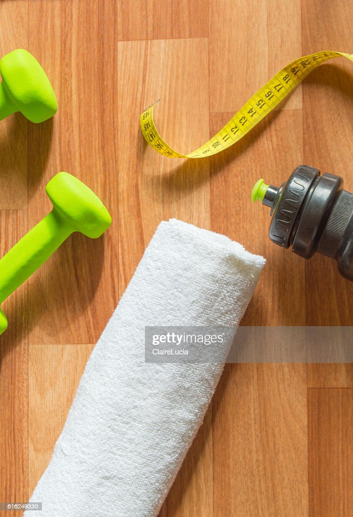 Fitness concept with dumbbells, water bottle, measuring tape, towel on : Stock Photo
