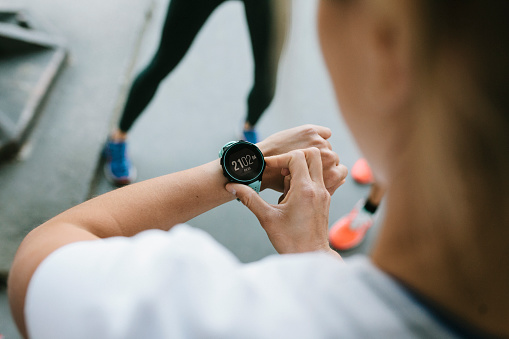 Fitness Enthusiast Setting Timer On Her Watch - gettyimageskorea