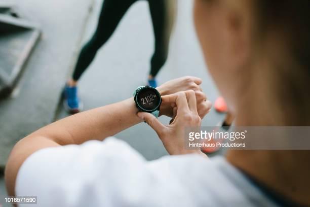 fitness enthusiast setting timer on her watch - polshorloge stockfoto's en -beelden