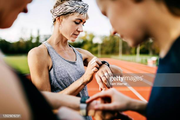 fitness enthusiasts checking their times after a run - fitness tracker stock pictures, royalty-free photos & images